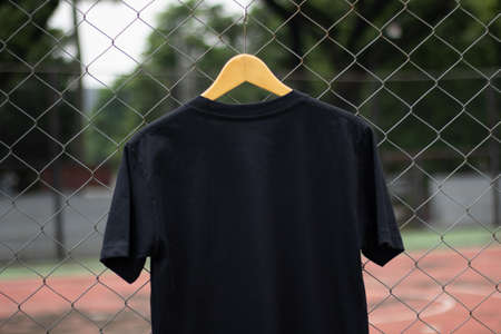 Blank black t-shirt on wood hanger in outdoor. Ready for your mock up design or presentation your design project.