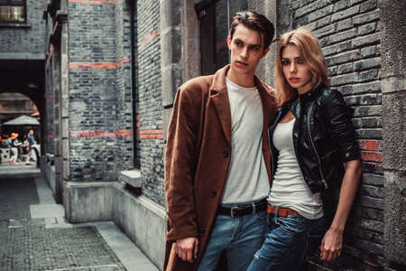 벽돌 벽과 거리의 포즈 젊고 트렌디 한 남자와 여자. 패션 스타일