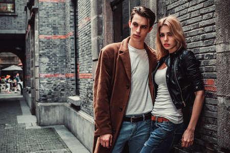 modelos masculinos: Hombre y una mujer joven y de moda posando de la calle con las paredes de ladrillo. Estilo de moda
