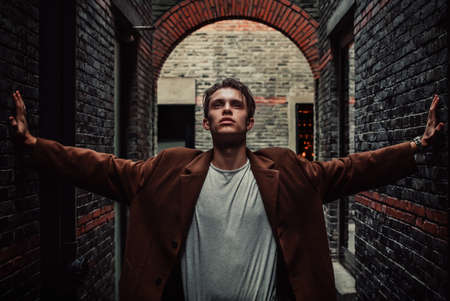 stylish man: Man in coat rests his hands on the wall and looking up near the brickwall. Fashion style.
