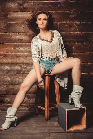 short shorts: Beautiful brunette girl in short shorts posing in studio on wooden background