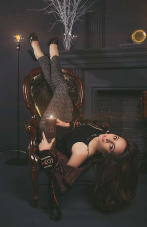 chear: Beautiful brunette girl in short shorts lying on the old vintage chear near fireplace. Studio shot. Stock Photo