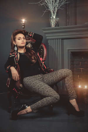 chear: Beautiful brunette girl in fashion clothes sitting posing on the old vintage chear near fireplace. Studio shot