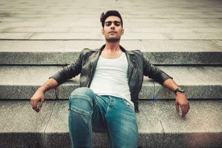 Homme élégant dans le t-shirt blanc, la veste en cuir et le jean debout près d'une colonne dans un environnement architectural moderne