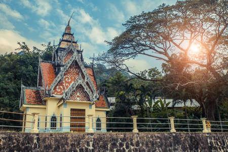 Ancient Thai temple. Wat Pa Aram Rattanaram Temple Phuket, Thailand. Big wonderful tree with sun.
