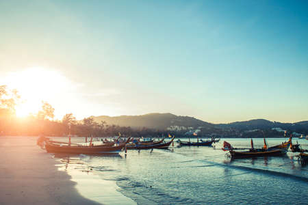 Longtale boat at the Thai beach. Paradice sand beach place. Boats on the clear water and blue sunrise sky. Banco de Imagens