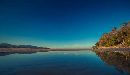 Colorful sky and the ocean smooth reflection in morning time before sunrise. Ocean simple beach panorama. Thailand