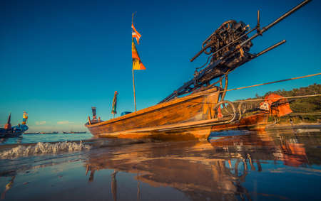 Longtale boat at the Thai beach. Paradise sand beach place. Boats on the clear water and blue sunrise sky.