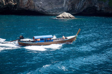 Wooden boat sailing on blue sea against rocks mountains.