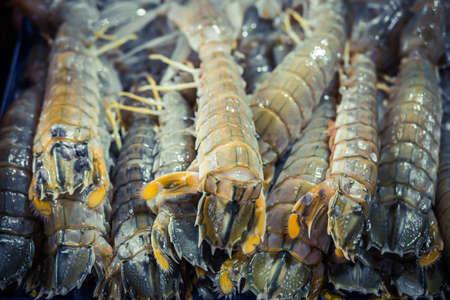 defrost: Crayfish Mantis shrimp pile in ice. Fresh seafood market. Stock Photo