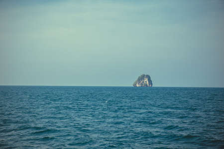 Island rock stand-alone over sea and blue sky wide shot background. Thailand Banco de Imagens
