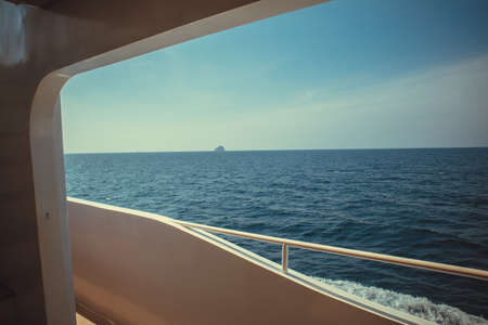 Luxury ship yacht window with a relaxing seascape ocean and blue sky view. Banco de Imagens