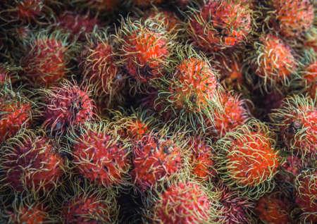 Pile of rambutan fresh fruit at market in Thailand.