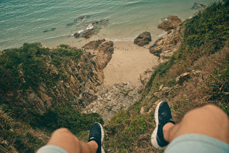Young brave man sitting on a high stone cliff above ocean. Top view.