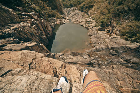 Young brave man sitting on a high stone cliff above little lake. Top view.
