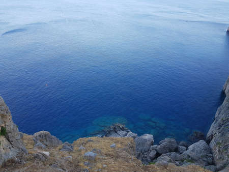 From above shot of clean blue water of calm sea near rough stony cliff on sunny day in beautiful nature. Banco de Imagens - 125394910