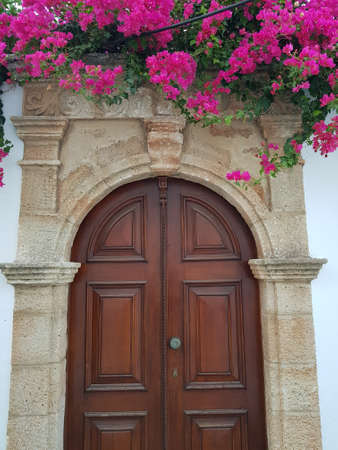 Shabby wooden door with pink red flowers in medieval sentury style.
