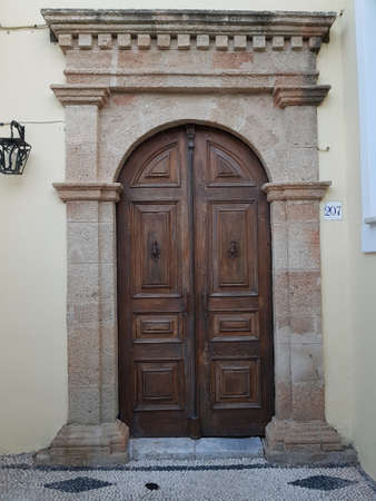Shabby wooden door in medieval sentury style of a white old house on the street of a old greec town. Banco de Imagens