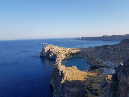 From above shot of clean blue water of calm sea near rough stony cliff on sunny day in beautiful nature. Banco de Imagens