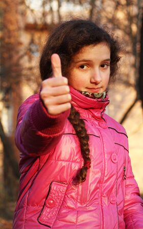 Portrait of beautiful young girl giving thumbs up Stock Photo - 11474467