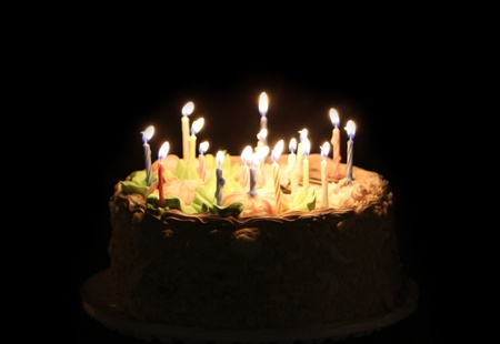 a year older: Birthday cake with candle isolated on black Stock Photo