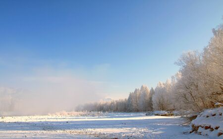 Winter landscape with snow trees and river in mountains  photo