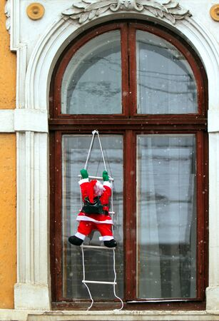 Santa climbing a ladder to get to the window. photo