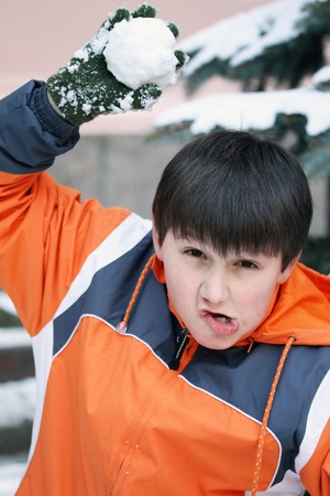 snowballs: Boy have fun with snowball fight winter outdoor Stock Photo