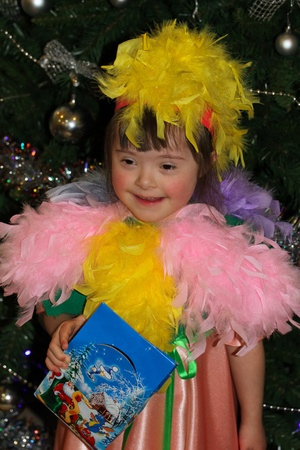 Smiling girl in fancy dress, holding gift on New Years holiday. photo