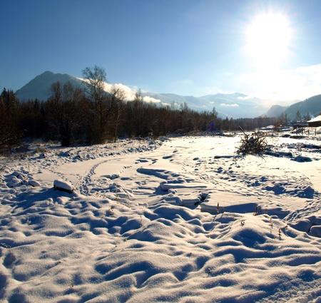 A Frozen River Multa in Russian Village Multa in winter in Uimon Valley, Altai mountains. photo