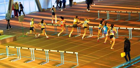 Women compete in the 60 meters hurdles