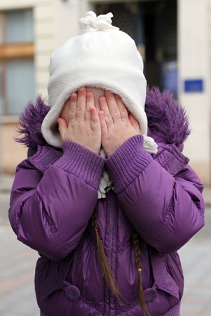 Little scared girl hiding face photo