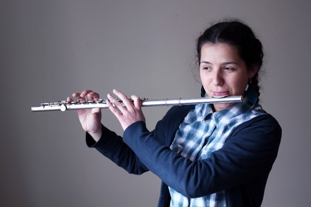 flute instrument: Teenage girl plays the flute.  Stock Photo