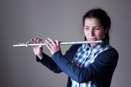 Teenager-Mädchen spielt Flöte. Standard-Bild