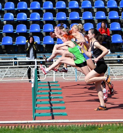 YALTA, UKRAINE - APRIL 25  Unidentified girls age 16-17 on the 100 meters hurdles race on Ukrainian Junior Track and Field Championships on april 25, 2012 in Yalta, Ukraine   Stock Photo - 13373067