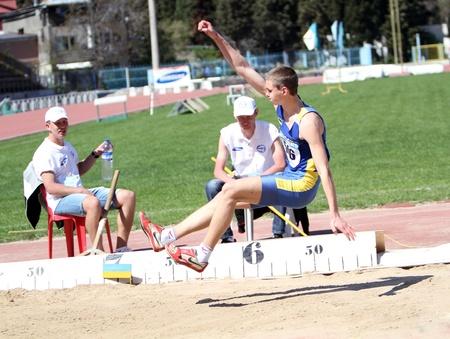 salto largo: Yalta, Ucrania - 25 de abril Reprshko Artem competir en el concurso de salto de longitud para la edad de 16 a 17 niños en la pista de Ucrania Junior y Campeonato de campo el 25 de abril de 2012 en Yalta, Ucrania