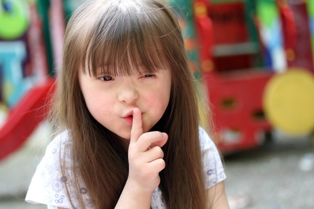 Down Syndrome: Portrait of beautiful young girl on the playground   Stock Photo
