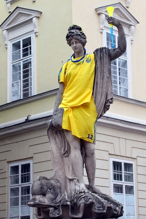 LVIV, UKRAINE - MAY 09: antique statue dressed in ukrainian national soccer uniform of EURO 2012 POLAND - UKRAINE, in the main square of Lviv on May 09, 2012 in Lviv, Ukraine.