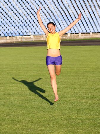 Beautiful teenage sport girl running on the grass  photo
