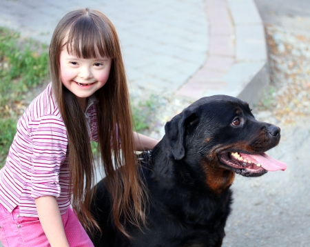 eyes looking down: Smiling little girl with a big black dog