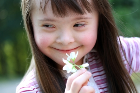 eyes looking down: Portrait of beautiful young girl with flowers in the park