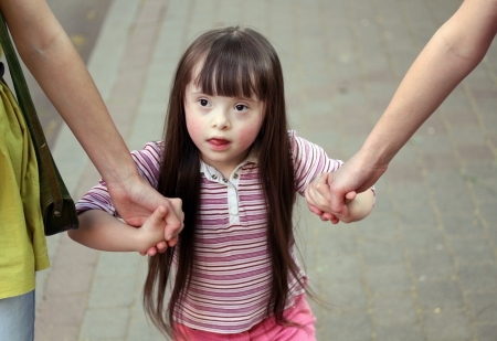 touch down: Girl holding arms of the sisters on a walk