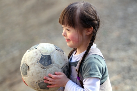 eyes looking down: Portrait of beautiful happy girl with a soccer ball