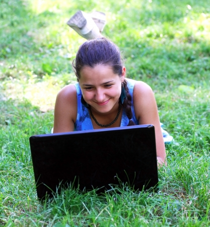 Happy woman outdoors with laptop photo