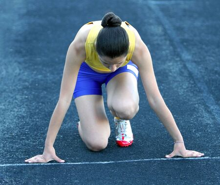 Athletic teenage girl in start position on track . photo