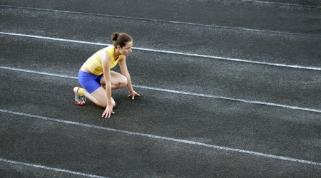 Athletic teenage girl in start position on track   photo