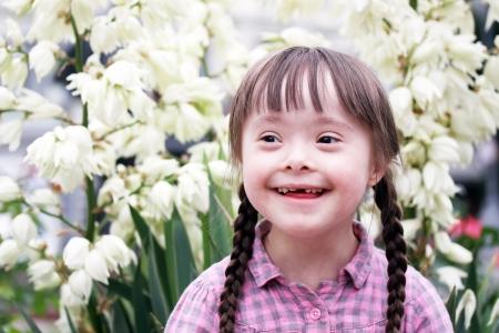 naar beneden kijken: Portret van mooie jonge meisje op bloemen achtergrond.
