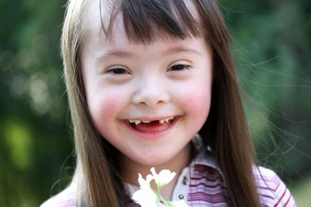 naar beneden kijken: Portret van mooie jonge meisje met bloemen in het park