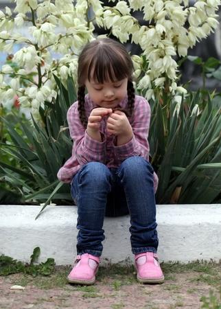 Belle jeune fille implantation sur fond de fleurs Banque d'images