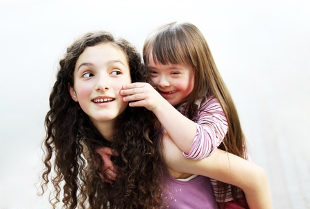 syndrome: Happy little girl with sister Stock Photo